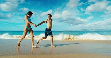 Couple holding hands walking down tropical beach in slow motion