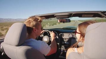 Pareja en viaje por carretera conduciendo en coche convertible rodado en r3d
