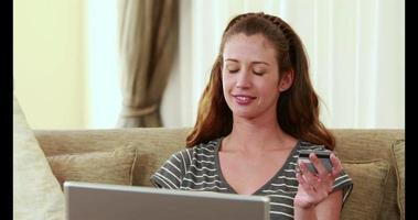 Mujer sosteniendo una tarjeta de crédito mientras escribe en una computadora portátil video