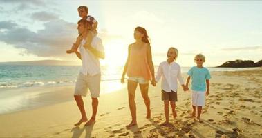 glückliche Familie am Strand bei Sonnenuntergang
