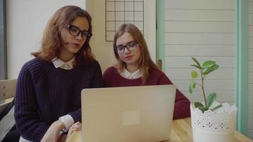 Two girls talking to friends via webchat or having a video chat in cafe