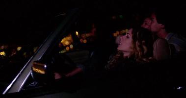Grupo de amigos sentados en un auto convertible retro por la noche