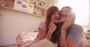 ragazze su un letto tenendosi i capelli come baffi