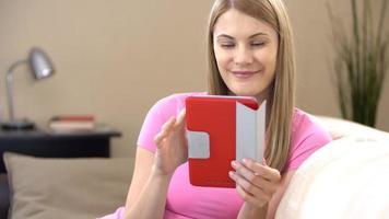 Beautiful attractive young woman in t-shirt with tablet sitting on sofa. Browsing Internet, smiling video