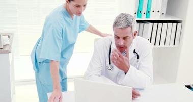 medici concentrati che esaminano laptop