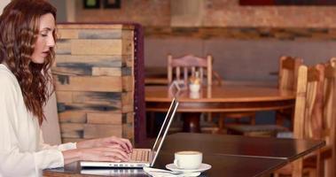 Mulher bonita tomando café enquanto usa o laptop video