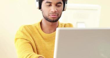 uomo sorridente con le cuffie utilizzando laptop