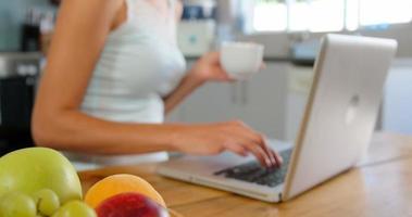 jolie blonde utilisant un ordinateur portable dans la cuisine