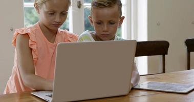 Two children using laptop with mother