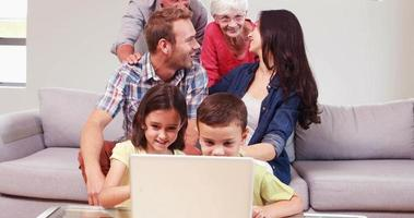 Sonriente familia multigeneracional usando laptop video