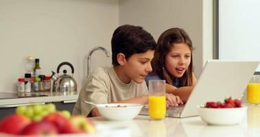 süße Geschwister mit Laptop beim Frühstück