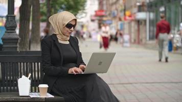 La empresaria árabe trabajando en un portátil al aire libre