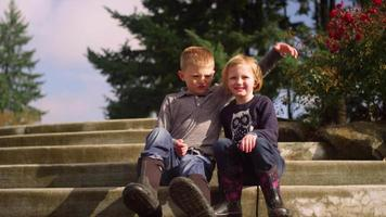 A young brother and sister smiling for a portrait on steps outside and starting to fight, slow motion video