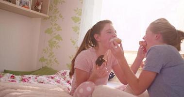 adolescentes se alimentando de rosquinhas em um quarto colorido