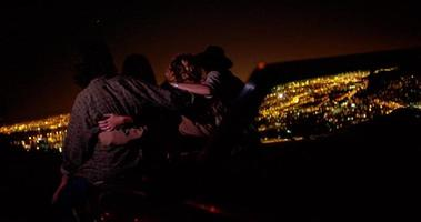 Los adolescentes abrazándose en un convertible mirando las luces de la ciudad de noche