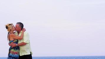 ein älteres Ehepaar küsst sich am Strand