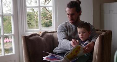 padre si siede sulla sedia a casa leggendo un libro al figlio girato su r3d video