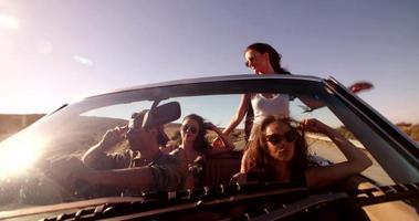 Gruppe glücklicher junger Leute auf Cabrio-Autoreise