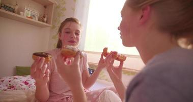 Chica adolescente comiendo una dona que su amiga la está alimentando