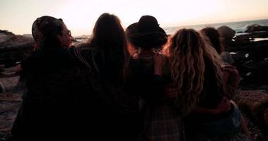 giovani amici adulti che abbracciano su un tramonto al mare