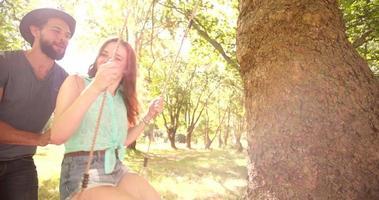 novio besando a su chica en el columpio del parque en cámara lenta