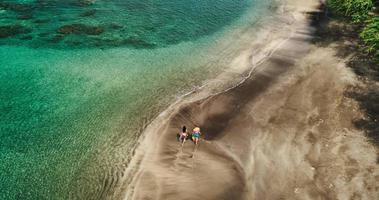 Vue aérienne du jeune couple marchant sur la plage tropicale en vacances