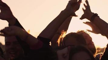 grupo de pessoas dançando e levantando as mãos ao ar livre na luz solar. tiro em câmera lenta.