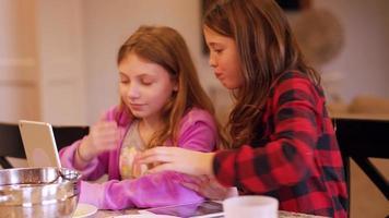 due amici seduti su un'isola della cucina usando le loro tavolette e mangiando spuntini video