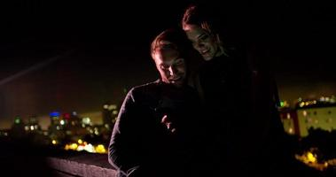 Young couple looking at smart phone on rooftop at night video
