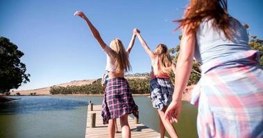 amici che corrono lungo un molo di legno in riva al lago