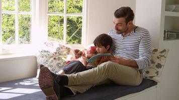 pai e filho lendo história em casa filmado em r3d