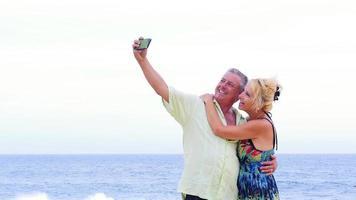 ein älteres Paar, das Spaß hat und Selfies am Strand macht