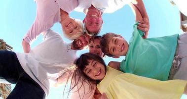 familia de tres generaciones de pie en un círculo sonriendo