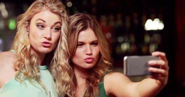 amigos sonrientes con champagne tomando selfie video