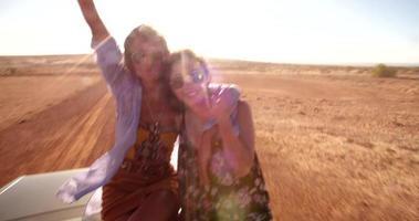 Amigas felices animando con los brazos levantados en un convertible video