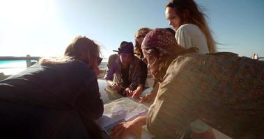 Amigos adultos jóvenes felices planeando su viaje por carretera en la playa