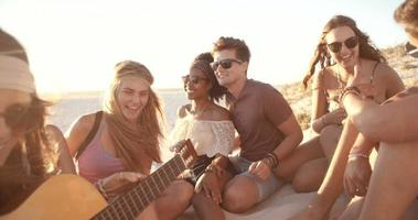 amici a una festa sulla spiaggia al tramonto con una chitarra