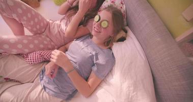 chicas adolescentes en pijama con pepino en los ojos
