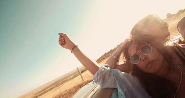 Amigos adolescentes riendo en un convertible durante un viaje por carretera