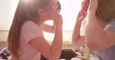 niñas sosteniendo donas en un dormitorio y riendo