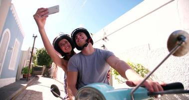 coppia su uno scooter prendendo un selfie video