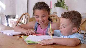 irmão e irmã colorindo foto na mesa
