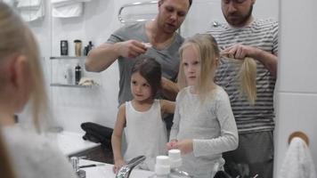 Gleichgeschlechtliches Paar, das Töchterhaare macht video