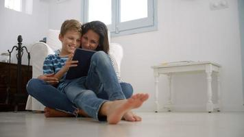 Mother And Son Sitting On Floor Using Digital Tablet video