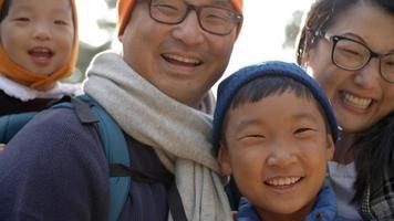 Mano cerca de una familia asiática de cuatro en un bosque
