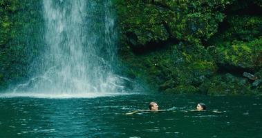 casal nadando para a cachoeira