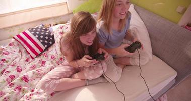 garotas na cama jogando no computador de pijama video