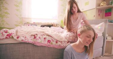 menina adolescente arrumando o cabelo da amiga no quarto dela