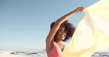 ragazza afro volare un panno in una giornata di sole in spiaggia