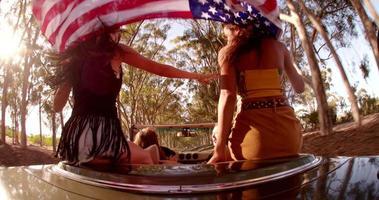 Freunde, die eine amerikanische Flagge während eines Road Trips halten